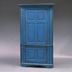 Blue-painted Corner Cupboard, America, 18th or 19th century, the upper section with dentil-molded cornice and paneled door opening to a four-shelf interior, the lower section with paneled cupboard door, raised on a bracket base, (imperfections), ht. 80 3/4, wd. 44, dp. 20 1/2 in.