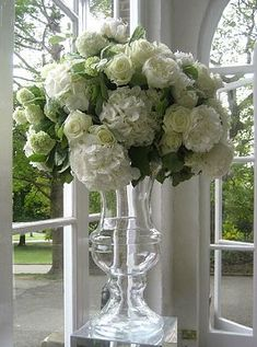 White and green floristry in clear glass urn