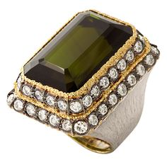 large scale Buccellati ring of 18K white and yellow gold featuring a large rectangular cut deep olive green tourmaline, surrounded by tiers of 54 diamonds approx. 4.5 carats, set on an imposing brushed gold shank with an upper rim of delicate openwork swags. M. Buccellati $100,000.00