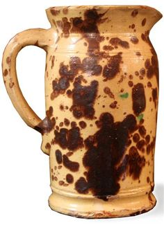 Glazed redware pitcher    attributed to solomon bell, strasburg, va, late 19th century    Flaring rim and spout on tall cylindrical form, yellow with brown splotches.    H: 9 1/2 in.        PROVENANCE:    The Collection of Mr. and Mrs. Jay Moyer, Lederach, Montgomery County, Pennsylvania. Sold for $ 1,400