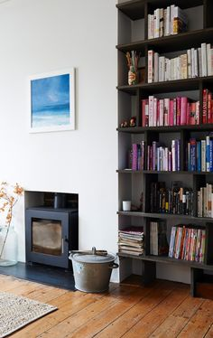 Wood stove and metal bucket, books arranged by color on Russel Bamber black bookshelf in Living Room of Anna Jones home in London | Remodelista