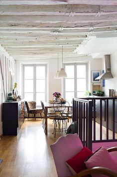 """Sneak Peek: Isabelle Rivoire-Grange. """"Everywhere in the apartment the ceiling is covered with irregular beams that I painted white. The kitchen was custom made. The bright pink neon light tints the entire apartment with a happy shade."""" #sneakpeek"""