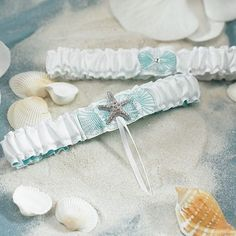 Complete your beachy wedding day look with the Seaside Allure Bridal Garter Set. The set includes a keepsake garter and a garter to toss at the recepetion. Each white satin garter features light blue seashell embroidery. The keepsake garter showcases a pretty silver starfish.