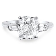 This luxurious platinum three stone engagement ring showcases a dazzling GIA certified cushion-shaped diamond with a D color grade and VS1 clarity. Two step cut bullet-shaped diamond accents grace the shoulders for a truly regal effect.