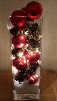 Vaas met dennenappels kerstballen sneeuw en lampjes