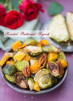 Roasted Brussels sprouts, peacans and butternut squash on a vingtage silver grey bowl. In the back, a green cloth with red roses - Roasted Vegetables