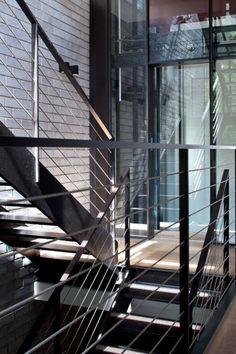 גופי תאורה שחורים מרובעים על קיר המדרגות