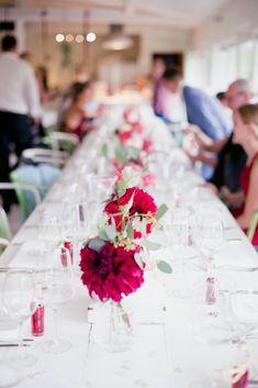 Eine schlichte Tischdekoration mit roten Blumen auf einem Hausboot.