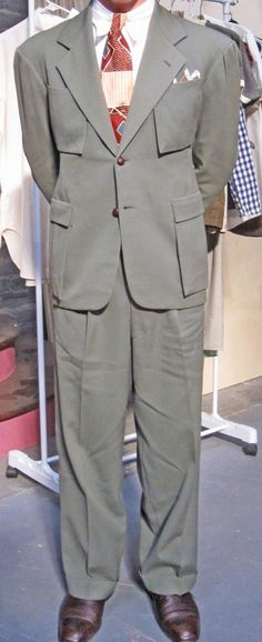Greyish green gabardine, 4 saddlebag pockets to the front, yoked belted back with shirring, pleated shoulders, tunnel belt loops. Truly a holy grail suit.