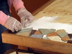Lady with gloves on adds broken colorful tiles to the top of the wooden table.