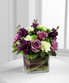 Beloved Bouquet-A sophisticated arrangement to offer your love and affection. Lavender roses, green carnations, purple stock, green hypericum berries, green button poms and lush greens are gorgeously arranged in a clear glass cubed vase lined with variegated ti leaves for a modern and stylish effect, making this a wonderfully romantic gift of sweetness set to brighten their day. #MissionViejoFlorist #MissionViejoFlowers #MardiGras #MardiGrasFlowers
