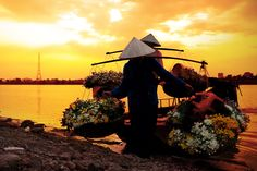 Two women carrying flowers off canoes at sunset
