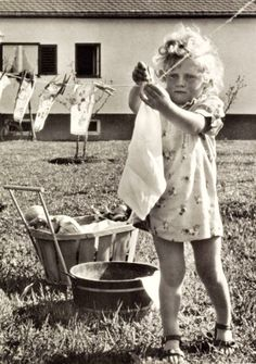 Vintage photo of a little girl hanging clothes on the clothesline