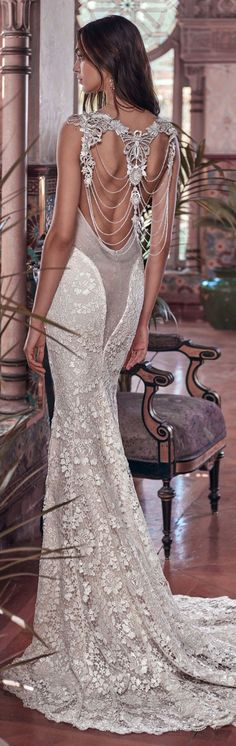 A mermaid column gown with a sheer back feature made of glistening French Guipure lace, bejeweled with Victorian embroideries and crystal strands on the back.