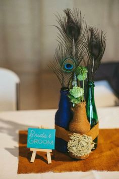 Wedding centerpiece wrapped bottles hops feathers twine burlap rustic peacock