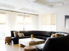 Jen Shalom's monochromatic Brooklyn loft. Caption: Black curved leather sofa, fur cushions, marble coffee table, brass vases, stools.