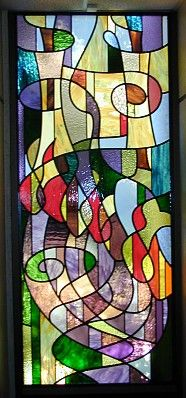These two stained glass windows are mounted on either side of the stage in the main sanctuary at the Beth Israel Synagogue in Greeley, Colorado. They are just over six and one half feet high, and are lit naturally with east-facing sunlight. There is a bush outside the window to the right, making the bottom a bit hard to see.