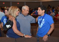 """Jose and Rhonda Carrasco of Anderson pass along encouraging words to their son JC Carrasco during a """"Passing the Mantle"""" ceremony, part of Orientation at Southern Wesleyan University. New students received medallions to mark the beginning of their educational and spiritual journey during the ceremony, which took place Aug. 15 in the auditorium of Newton Hobson Chapel and Fine Arts Center."""