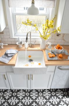 woodtop counter top + white kitchen + pattern tile flooring