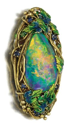 GOLD, ENAMEL AND OPAL BROOCH, LOUIS COMFORT TIFFANY, CIRCA 1910.  Centring on a black opal within a textured surround of fruiting vine leaves decorated with blue and green enamel, accented with circular-cut sapphires and green garnets, signed Tiffany & Co.