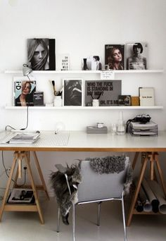 White study with white shelves and black and white photos