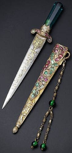 Ottoman minature dagger, green glass hilt, the quillons set with rubies and emeralds, gold damascened inscribed blade, gilt scabbard with further rubies, emeralds and chased to depict a trailing vine, scale design chape, suspension loop with a chain ,faceted sections, green glass beads, 11.7 cm. long, with the tugra of Princess 'Adile Sultana (1825 -1898), the daughter of Sultan Mahmud II (1785-1839) and sister of the Sultans Abdulmecid I and Abdulaziz.