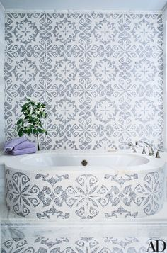 The master bath, decorated with mosaic tilework, has a BainUltra tub.