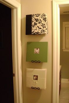 use plate hangers to display photo albums. This is so much more awesome than having them rot on a shelf! Genius :]