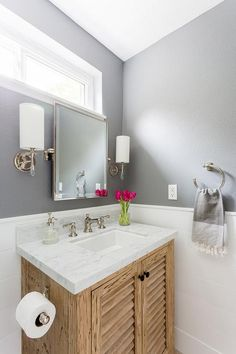 Light charcoal gray bathroom walls paired with shiplap completed with a light wood shutter single vanity, oil rubbed bronze knobs, white marble countertop and vintage sink faucet.