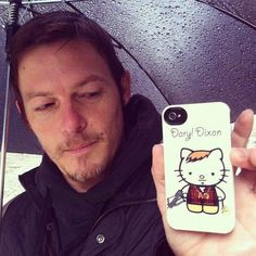 Please enjoy this photo of Norman Reedus and his phone cover featuring Hello Kitty as Daryl Dixon.