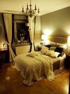 Neutral walls, white bedding, chandelier (bedroom)
