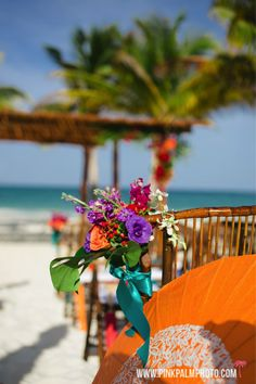 Bright tropical florals were placed on ceremony aisle chairs accenting the beautiful beach!  #mishkadesignsmexico #secretsmaroma