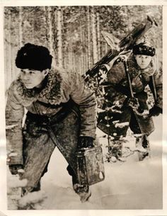 """1940- Red Army machine gun team moving their weapon through a snow-covered wood to a new position """"somewhere"""" in Finland."""