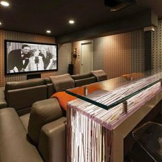 Home theater design by Wendy Eigen Designs with custom bar by Cliff Young, acrylic barstools and leather sectionals from Cliff Young with reclining features and built-in cupholders.