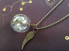 This is a cute, real Dandelion Seed necklace in a glass wish globe and little Peacock feather charm attached to it.  The necklace will arrieve your home in a cute gift wrap