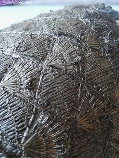 Čepec pro vdanou ženu, podložený tvrdým papírem, pošitý stříbrnými paličkovanými krajkami (motiv vějířků), dýnko čepce zdobené výšivkou stříbrným kovovým bouillonem (drátkem), penízky (flitry) stříbrné barvy a plechovými perlemi stříbrné barvy, vzor plastický, motiv kytice s květy. Obličejovou část lemuje bílá paličkovaná krajka s motivem stonku s květy. Vzadu přišitá hedvábná stuha uvázaná do mašle. Tento čepec může pocházet ze středních, východních nebo severovýchodních Čech. Stáří cca 150…