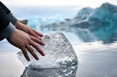 person with hands on ice block on water during daytime photo – Free Ice Image on Unsplash