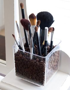Coffee beans in a glass to store make-up brushes. Lovely.