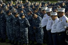 """Service members and civilian first responders bow their heads in pray at the """"Missing Man Memorial"""" at Joint Base Pearl Harbor-Hickam, Hawaii during a Patriots Day ceremony to commemorate the 11th anniversary of the 9/11 terrorist attacks at the World Trade Center, Pentagon, and Flight 93. Sept. 11, 2012. (Department of Defense photo by U.S. Air Force Tech. Sgt. Michael R. Holzworth/Released)"""