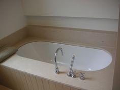 Onderbouw bad afgewerkt met natuursteen. Inbouwkraanwerk: Dornbracht Tara Classic. Landelijke stijl.