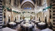 Dinner room set up: white almond blossom flowers hanging from the ceiling and glass boules lighting. White flowers centerpiece and jasmine background walls.