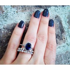 A non-traditional engagement ring for a non-traditional girl. Featured is our 2.05ct oval rich deep blue sapphire halo diamond ring. Shown with two modern diamond bands. #sapphire #halo #engagementring