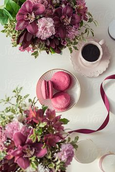 Beautiful workplace with flowers bouquets, coffee cup, ribbon and macaroons
