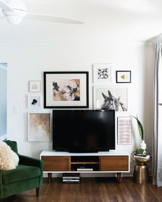 Gallery wall, white + wood entertainment center with green and metallic accessories.