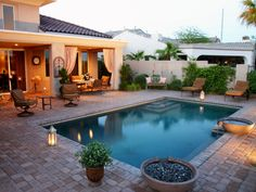 Small, tumbled pavers surround the pool and extend throughout the patio area to give this small backyard the illusion of a larger space.