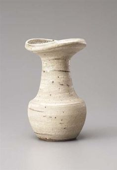 Vase with flaring lip, Stoneware. The mineral elements mixed into the body material combining with the light-brown glaze creating a streaked and speckled surface. 26 cm. (10 1/4 in.) high, c.1979