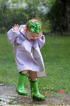 A flood of happiness wearing smiley  green galoshes and a green poke-a-dot bow on her head.