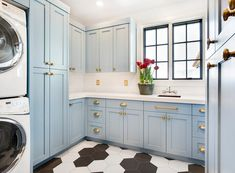 Gorgeous blue and white laundry room features black and white mixed hexagon floor tiles complementing blue shaker cabinets adorned with brass hardware and a white quartz countertop.
