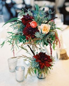 Garden inspired wedding decor of greenery, red dahlias, blush roses, coral ranunculus and thistle.