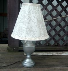 From shiny brass to fabulous! Plus a fabric covered shade to go with it! I have had this lamp for many, manyyears and the shade was in the attic. Say bye, bye brass and nasty shade… First I lightly sanded the lamp, then masked, and primed with a grey primer. I then found this gorgeous …
